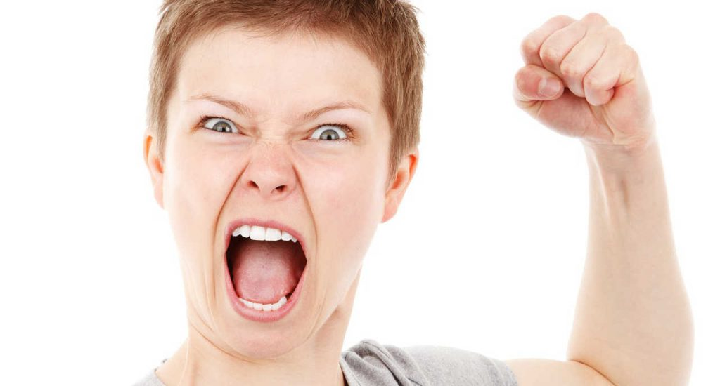 An angry person yelling with a raised fist who would benefit from anger management